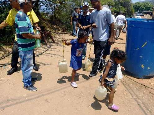 Niños obligados a cargar agua en sectores populares